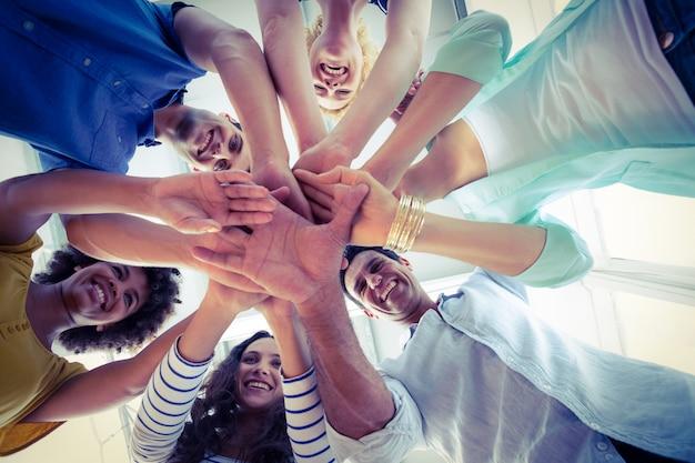 Équipe créative rassemblant ses mains