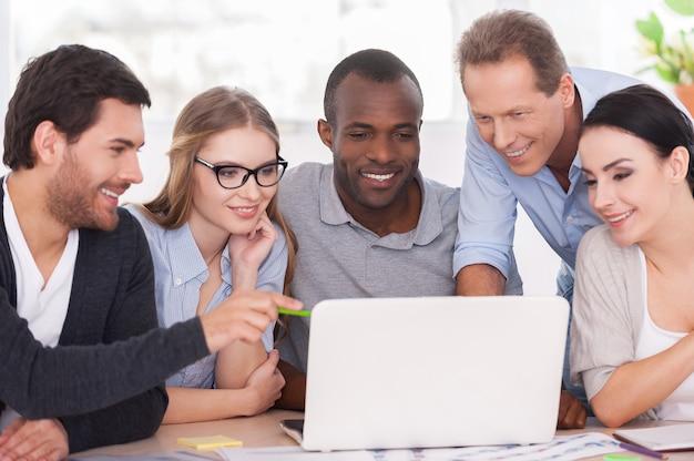 Équipe créative travaillant sur le projet. groupe d'hommes d'affaires en tenue décontractée assis ensemble à la table et regardant l'ordinateur portable
