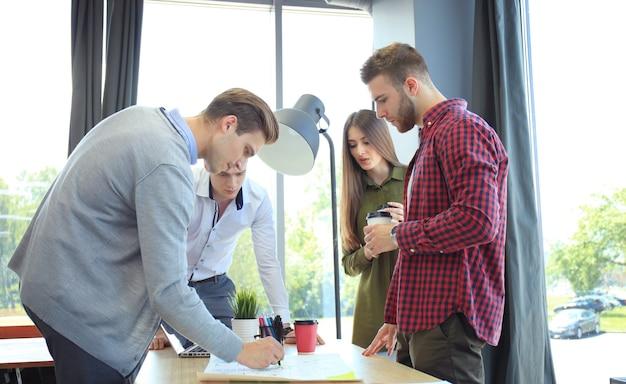 Équipe de démarrage d'entreprise lors d'une réunion dans un brainstorming intérieur de bureau moderne et lumineux, travaillant sur un ordinateur portable et une tablette.