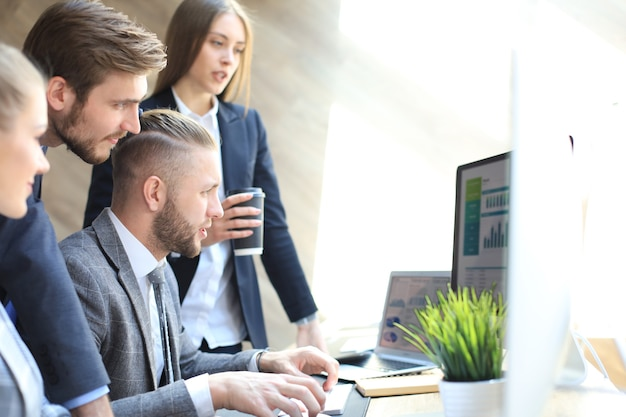 Équipe de démarrage d'entreprise lors d'une réunion dans un brainstorming intérieur de bureau moderne et lumineux, travaillant sur des ordinateurs tablettes et pc.