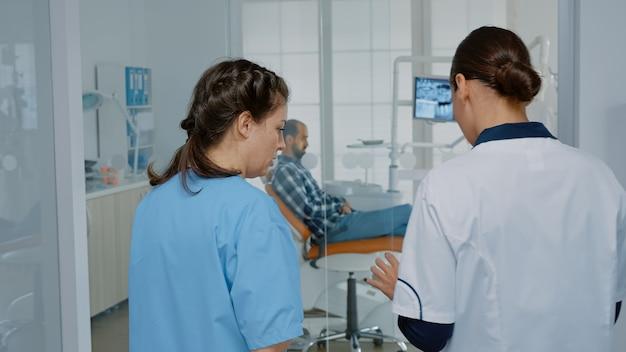 Équipe de dentisterie discutant de la procédure à l'aide de rayons x sur tablette