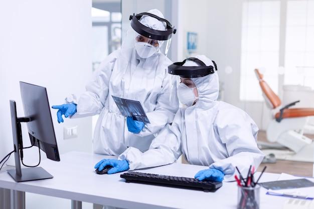 Équipe de dentisterie fatiguée vêtue d'un costume ppe pendant covid-19. spécialiste médical portant un équipement de protection contre le coronavirus lors d'une épidémie mondiale en regardant la radiographie dans un cabinet dentaire.