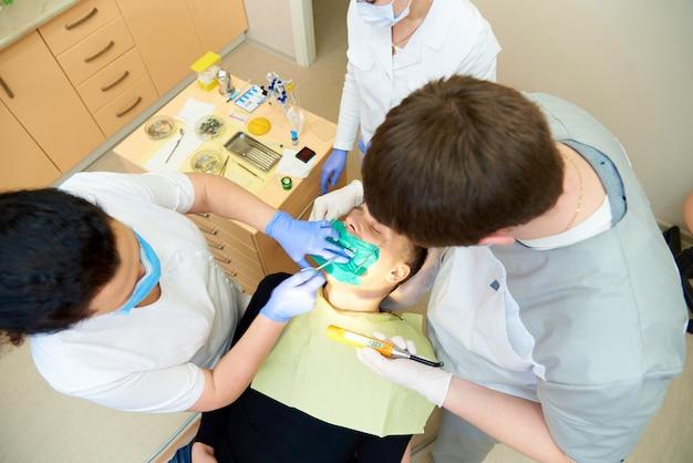 Une équipe de dentistes traite les dents d'un patient dans une clinique dentaire.