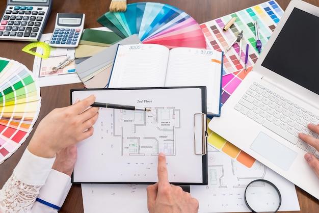 Équipe de designers créatifs discutant du plan de la maison au bureau