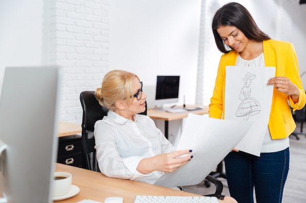 Équipe de deux femmes architectes sérieuses discutant de croquis au bureau