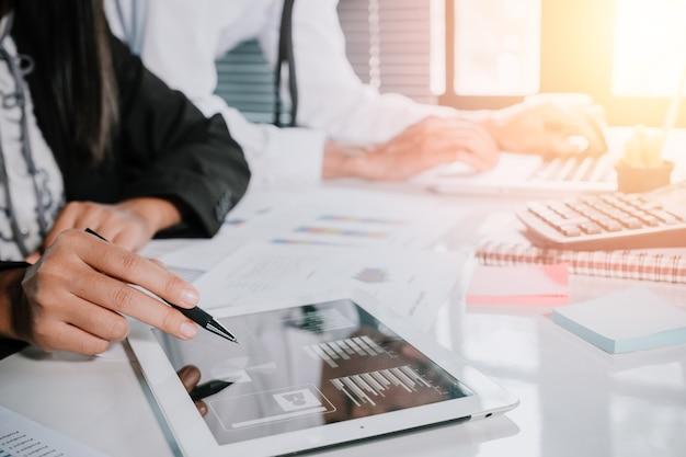 Équipe de deux jeunes entrepreneurs à l'aide de tablette tactile et ordinateur portable à la réunion. concept d'entreprise et de la stratégie.