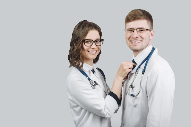 Équipe de deux médecins homme et femme debout étroitement souriant tout en regardant la caméra isolée sur fond gris avec espace copie