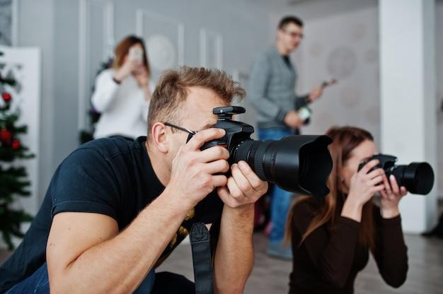 L'équipe de deux photographes photographiant en studio derrière trois autres travailleurs. photographe professionnel au travail. cours de maître.