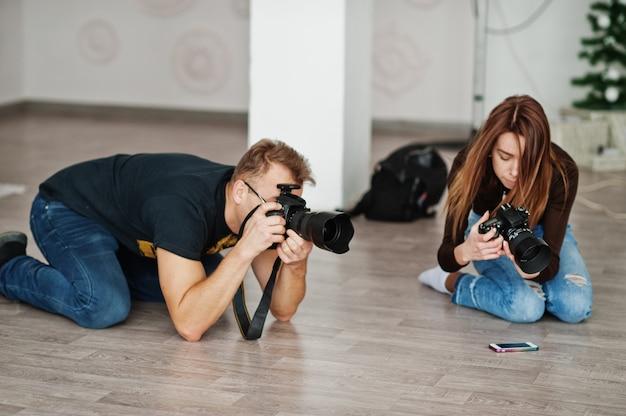 L'équipe de deux photographes photographiant en studio à genoux. photographe professionnel au travail. cours de maître.