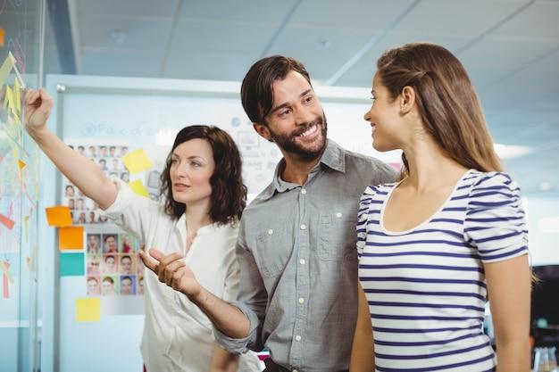 Équipe de dirigeants d'entreprise discutant de notes autocollantes