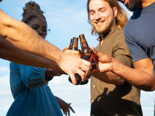Équipe diversifiée d'amis célébrant un événement festif à l'extérieur