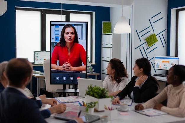Équipe diversifiée de collègues discutant avec le chef de projet à l'aide d'une webcam lors d'une conférence d'affaires assise dans une salle d'audience