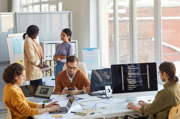 Équipe diversifiée de développeurs informatiques utilisant des ordinateurs et du code de programmation tout en collaborant à un projet dans un studio de production de logiciels