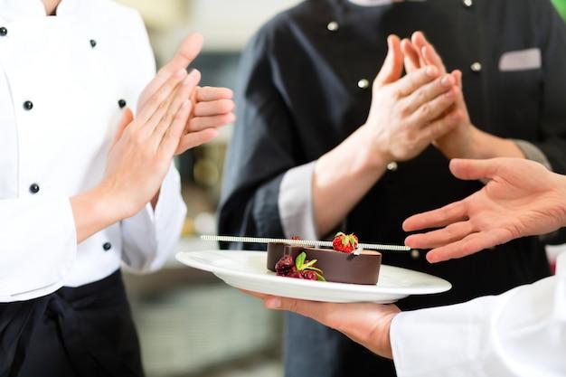Équipe du chef dans la cuisine du restaurant avec dessert