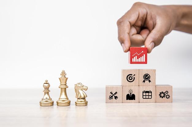 Équipe d'échecs debout avec une pile de blocs en bois cube avec l'icône de l'entreprise.
