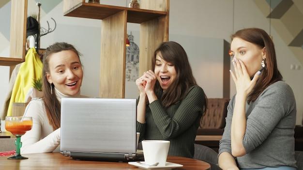 Équipe de femmes réussies dans un centre de coworking: lecture d'un message avec de bonnes nouvelles dans un ordinateur portable puis se donner un cinq. vue de face