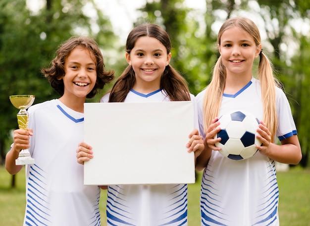 Équipe de football gagnante tenant une carte vide
