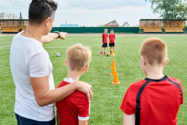 Équipe de football junior pratiquant sur le terrain