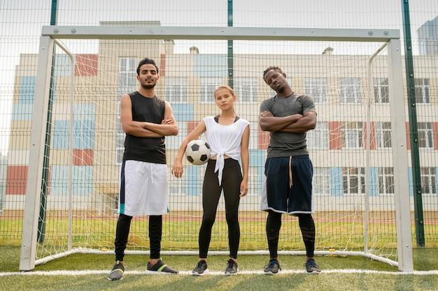 Équipe de football universitaire composée de gars interculturels et fille de race blanche debout sur le terrain par net