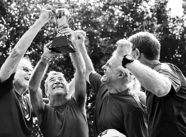Une équipe de footballeurs matures remportant la coupe
