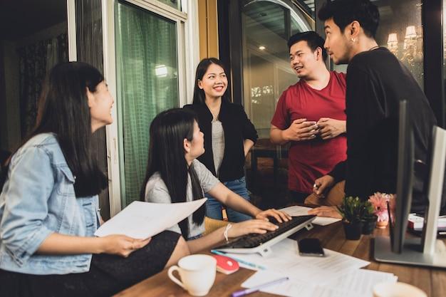 Une équipe freelance asiatique en conversation avec un bureau à la maison