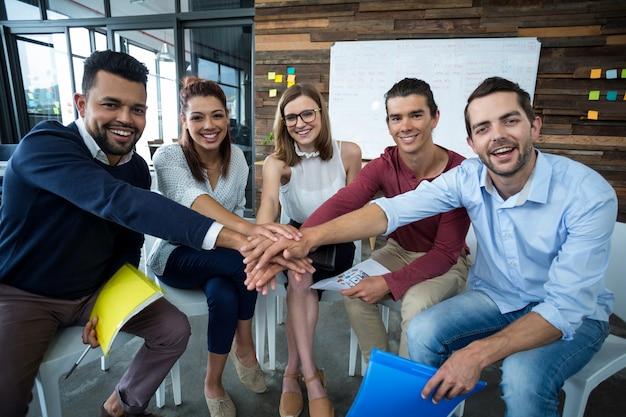 Équipe de gens d'affaires formant pile de main au bureau
