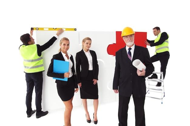 Équipe de gens d'affaires et de travailleurs assemblant un puzzle isolé sur blanc