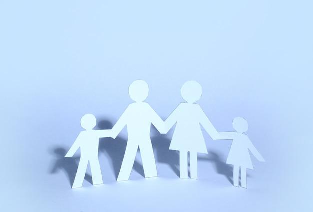Équipe de gens de poupée de papier se tenant la main