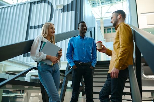 L'équipe de gestionnaires parle dans les escaliers dans le bureau informatique