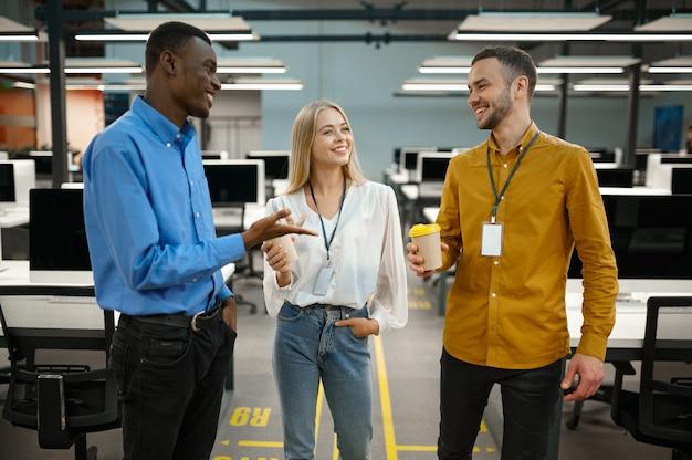 Équipe de gestionnaires avec des pourparlers de café au bureau informatique. travail d'équipe et planification professionnels, brainstorming de groupe et travail d'entreprise, intérieur d'entreprise moderne en arrière-plan