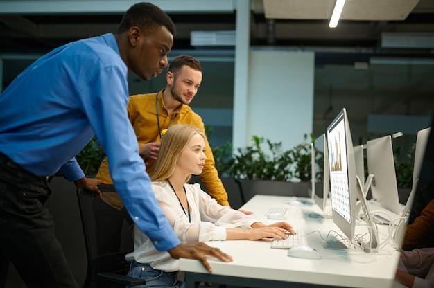L'équipe de gestionnaires regarde à l'écran dans le bureau informatique