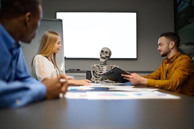 Équipe de gestionnaires et squelette dans le bureau informatique, blague