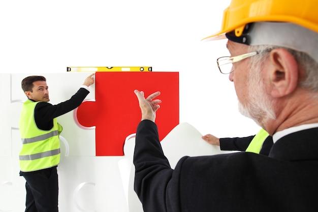 Équipe d'homme d'affaires et de travailleurs assemblant un puzzle isolé sur blanc