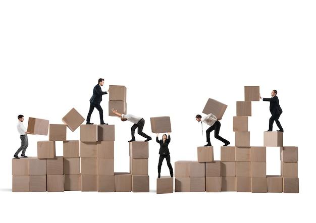 Une équipe d'hommes d'affaires construit une construction avec des cubes de bois