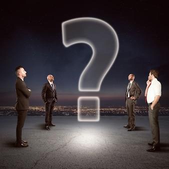 Une équipe d'hommes d'affaires regarde ensemble un grand point d'interrogation