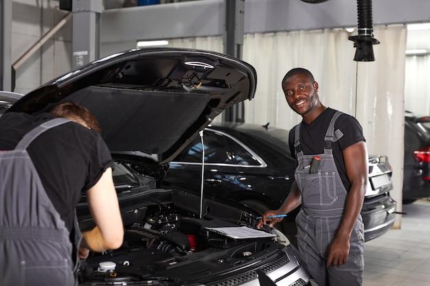 Équipe d'hommes africains et caucasiens travaillant ensemble dans le service automobile
