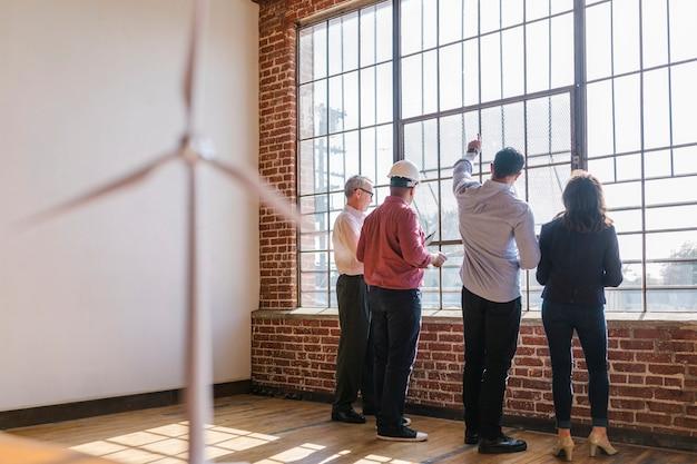 Équipe d'ingénierie respectueuse de l'environnement discutant par les fenêtres en verre
