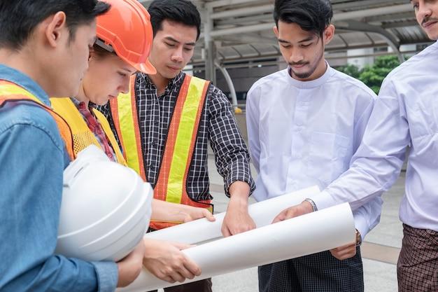 Équipe d'ingénieurs avec un homme d'affaires du myanmar tenant une réunion de plan directeur et discutant du projet de construction dans la ville