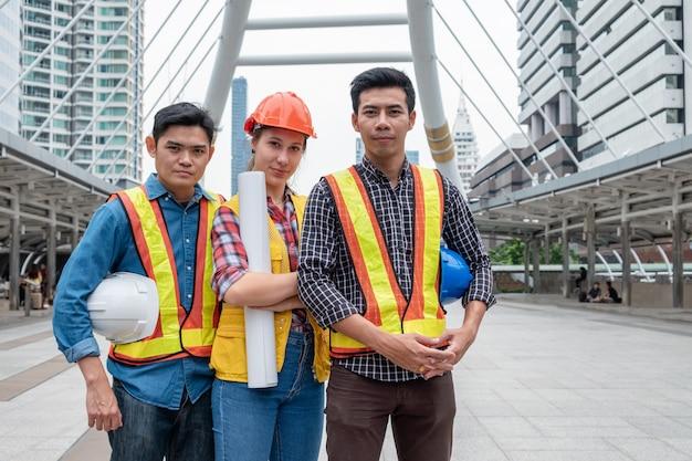 Équipe d'ingénieurs multiethniques confiant debout et tenant un plan, casque de sécurité sur un chantier de construction en milieu urbain