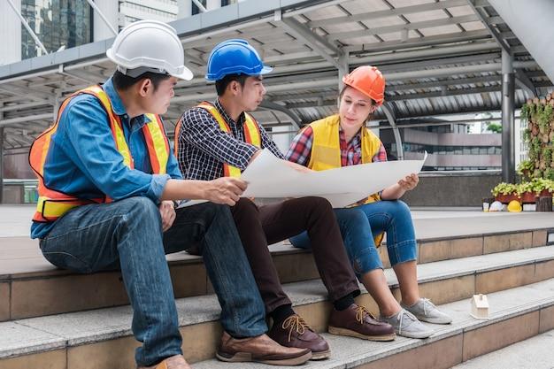 Équipe d'ingénieurs multiethniques se réunissant et discutant avec un plan pour un nouveau projet de chantier de construction en milieu urbain