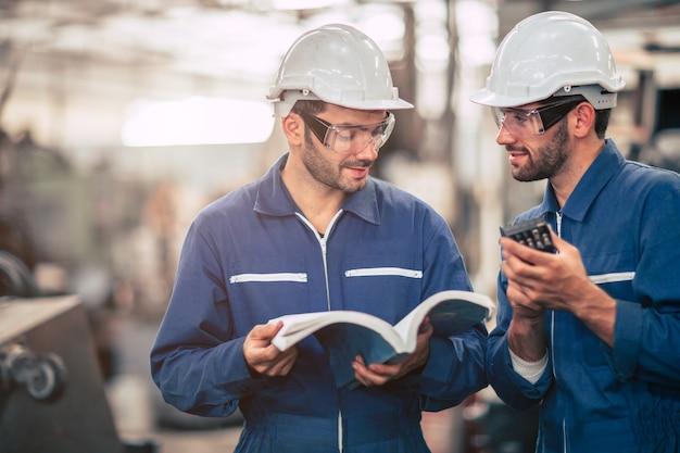 Une équipe d'ingénieurs parlant ensemble enseigne et apprend des techniques d'ingénierie sur l'utilisation de la machine avec un manuel d'instructions ouvert sur le lieu de travail de l'usine.