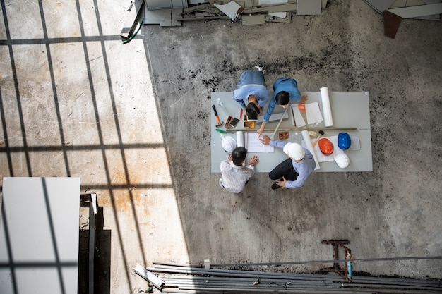 Une équipe d'ingénieurs de quatre personnes discutent ensemble pour examiner les matériaux de construction et lancer un brainstorming