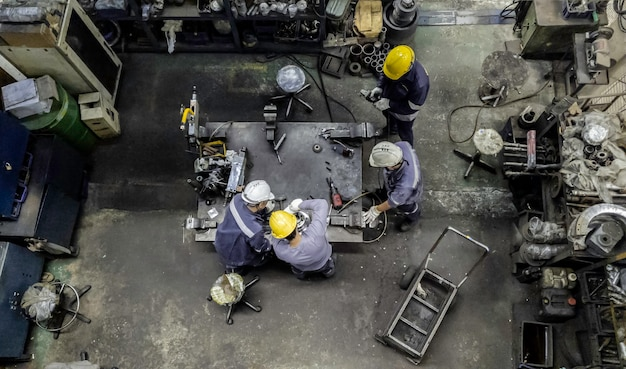 L'équipe d'ingénieurs travaille dans la salle d'atelier, le technicien répare et répare la partie de la machine en usine, ton vintage, vue de dessus