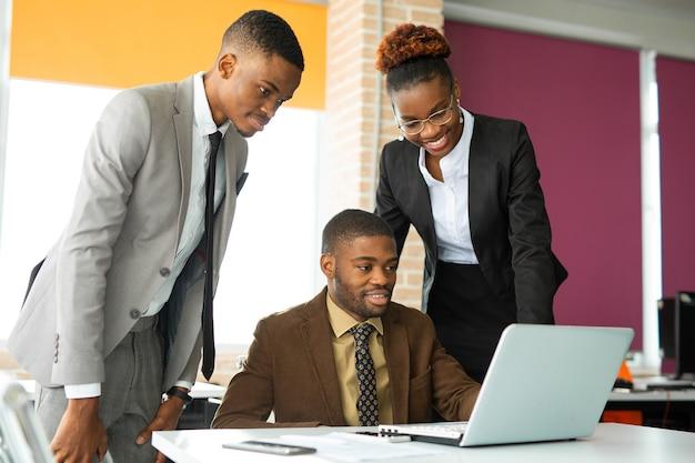 Équipe de jeunes africains au bureau à la table avec un ordinateur portable