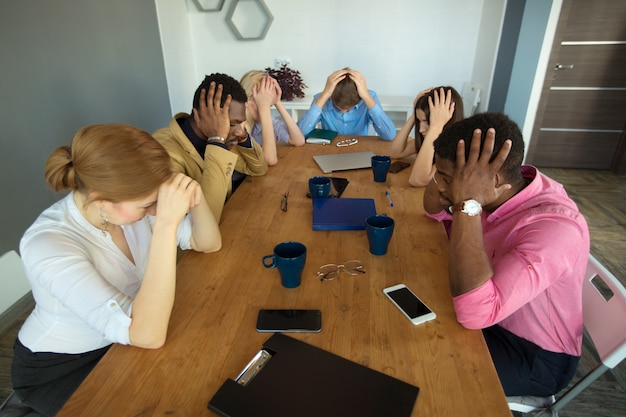 Équipe de jeunes belles personnes au bureau à la table