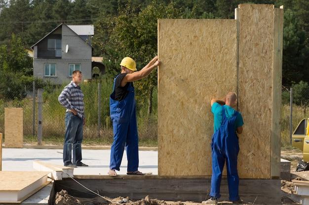Équipe de jeunes constructeurs érigeant des panneaux muraux préfabriqués sur un chantier de construction d'une nouvelle maison