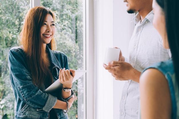 Équipe de jeunes entrepreneurs asiatiques heureux souriant et se détendre tout en réunion