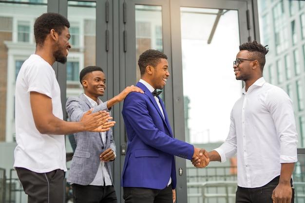 Équipe de jeunes hommes africains près du bâtiment se serrer la main