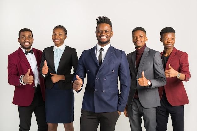 Équipe de jeunes hommes et femmes africains beaux en costume avec geste de la main