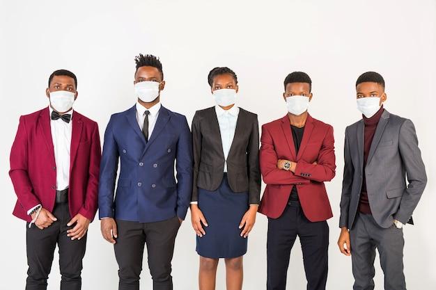 Équipe de jeunes hommes et femmes africains beaux en costumes dans des masques de protection